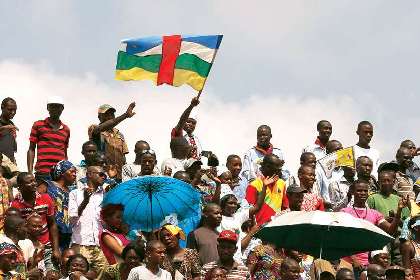 A man waves the national flag of the Central African Republic as Pope Francis celebrates Mass in Barthelemy Boganda Stadium in Bangui, Central African Republic, Nov. 30.
