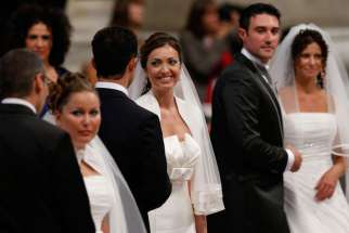 Newly married couples react after exchanging vows in St. Peter's Basilica at the Vatican Sept. 14, 2014. Among those married were couples who already had children or have lived together before marriage.
