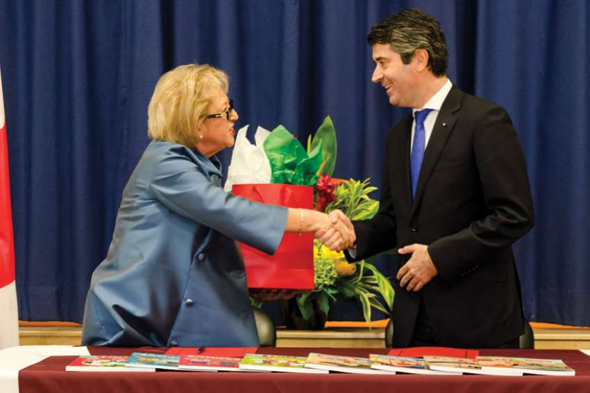Angela Gauthier, left, and José Luis Carneiro seal the deal between Toronto's Catholic school board and the Portuguese government with a hand shake.