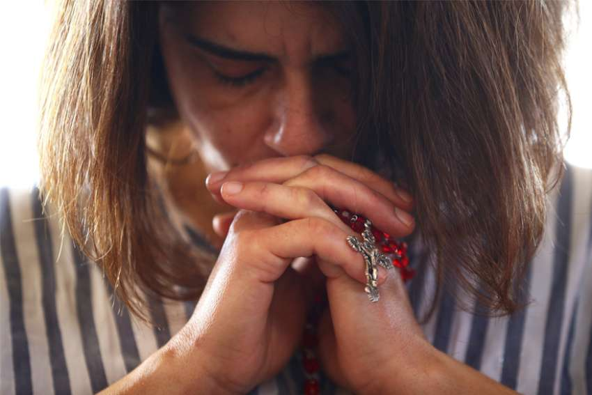 A woman holding a rosay prays during Mass at a church in Beirut Aug. 9, 2020. The church was damaged five days earlier in explosions in Beirut's port area. Cardinal Bechara Rai, Maronite patriarch, described the shrinking presence of Christians in the Middle East as a sinking ship to leaders of the Middle East Council of Churches Sept. 18.