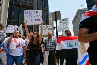 Protesters display signs and carry flags during a 2014 protest in Detroit, calling on the U.S. to intervene in the persecution of Christians in Iraq.