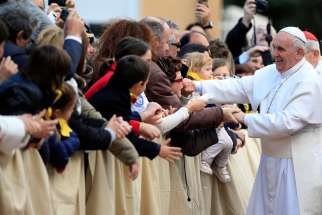 Pope Francis greets the faithful as he arrives at the Our Lady of Providence Center in Rome April 17, 2015. Vatican officials announced the Pope will celebrate the Holy Thursday Mass of the Lord's Supper with young refugees in Castelnuovo di Porto, about 15 miles north of Rome.