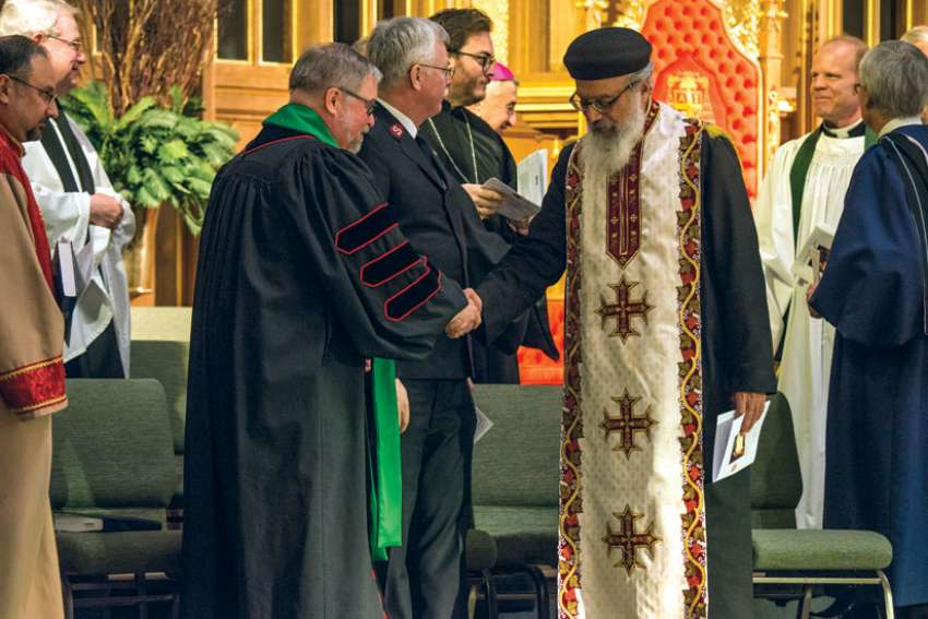 Rev. Dr. Peter Holmes, left, offers the sign of peace to Orthodox Coptic Fr. Bishoi Wasfy at a service to wrap up the Week of Prayer of Christian Unity held at St. Michael's Cathedral Basilica Jan. 29.