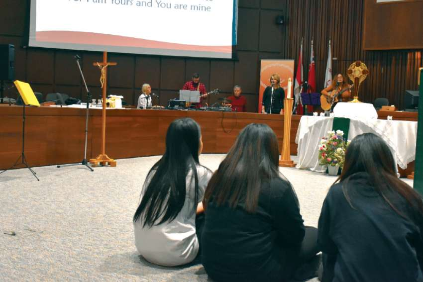 Three students moved closer to the Blessed Sacrament during a guided Adoration at a Young Disciples event at Toronto's Catholic Education Centre.