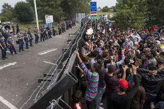 Migrants stand in front of a barrier at the border with Hungary near the village of Horgos, Serbia, on Sept. 16, 2015.