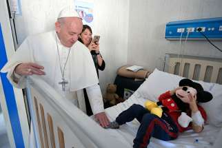 Pope Francis greets a patient during an unannounced visit to the Palidoro Bambino Gesu Hospital, in Fiumicino, outside Rome, in this Jan. 5, 2018, file photo.