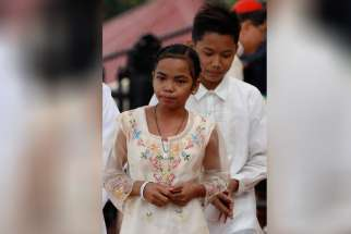 Glyzelle Palomar, 12, and Jun Chura, 14, two former street children, walk to their seats after greeting Pope Francis during a meeting with young people at the University of St. Thomas in Manila, Philippines, Jan. 18.