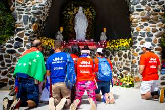 World Youth Day pilgrims pray before Our Lady of Perpetual Help during opening-day festivities in a Panama City park Jan. 22, 2019.