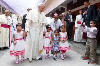 Pope Francis walks with children as he visits the Mother Teresa House in the Tejgaon neighborhood in Dhaka, Bangladesh, Dec. 2.