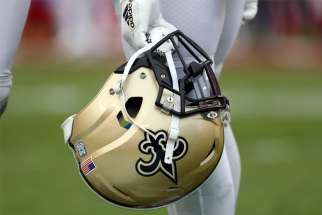 "A New Orleans Saints player is seen holding his helmet during the second half of a game in 2019. In a Jan. 24, 2020, story, The Associated Press claimed the Saints' owner, a devout Catholic, has aided the New Orleans Archdiocese in trying to shield emails related to the sex abuse crisis. The archdiocese in a statement called the story false, saying its only advice on the matter was to ""be direct, open and fully transparent."""