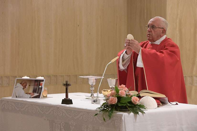 Pope Francis celebrates a memorial Mass for Father Jacques Hamel in the chapel of the Domus Sanctae Marthae at the Vatican Sept. 14. Father Hamel, seen in the photo on the altar, was murdered while celebrating Mass in Rouen, France, July 26; the two killers claimed allegiance to the Islamic State group.