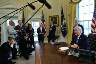 U.S. President Donald Trump talks to journalists in the Oval Office at the White House March 24. After the Senate released its health care bill June 22, the Congressional Budget Office said the measure would leave 22 million more people uninsured.