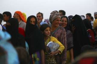 "Iraqi refugees line up to receive free food inside the Khazer camp on the outskirts of Irbil, Iraq, June 29. Archbishop Bashar Matte Warda of Irbil told Catholic New Service by telephone June 28 the situation was going ""from bad to worse."""
