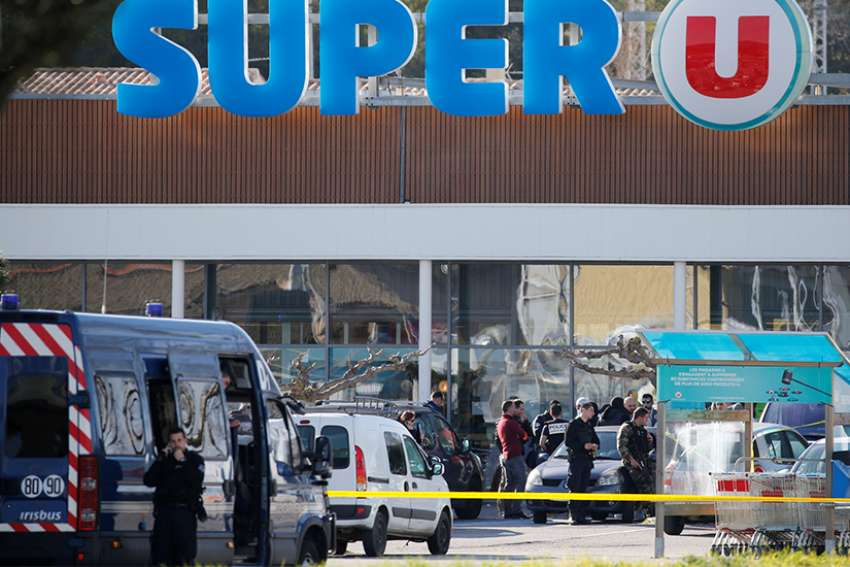 "French police officers and investigators are seen March 23 at a supermarket after a hostage situation in Trebes. Pope Francis joined leaders praising a French police officer who ""gave his life out of a desire to protect people"" during a terrorist attack."