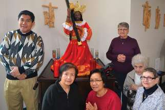 Fr. Nilo Macapinlac (left) and other devotees of the Black Nazarene statue currently at Sacred Heart parish in Wetaskiwin, Alta.