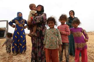 A displaced Syrian family who fled violence in Aleppo stands in a field in the rural area of Manbij in 2016. Amid the destruction in war-torn Syria, a community of Discalced Carmelites in Aleppo perseveres in its mission of continuous prayer and help to families in need.