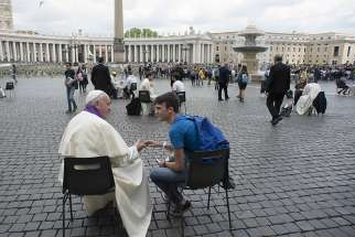 Pope Francis hears confession of a youth April 23, 2016 in St. Peter's Square at the Vatican.