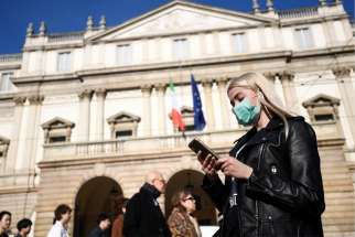 A woman wearing a face mask checks her phone outside the Teatro alla Scala opera house, closed by authorities due to a coronavirus outbreak in Milan Feb. 24, 2020. The Archdiocese of Milan issued a notice Feb. 23 suspending all public celebrations of Mass until further notice in compliance with Italian Ministry of Health precautions to prevent the further spread of the coronavirus.