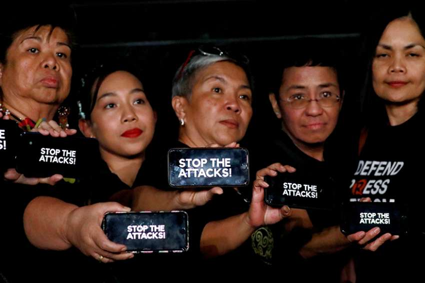 "Journalists, including Rappler CEO Maria Ressa, raise their smart phones with words ""STOP THE ATTACKS!"" in a rally for press freedom in Quezon City, Philippines, Feb.15, 2019. Church leaders across Asia have expressed alarm over threats to press freedom amid reports of increasing attacks and intimidation of journalists, resulting in growing levels of self-censorship."