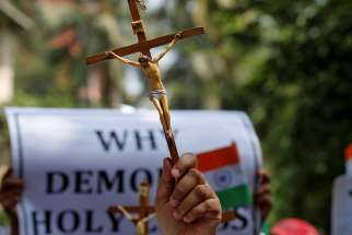 A woman holds a cross during a May 3 protest in Mumbai, India, organized by various Catholic organizations against what they say is an illegal demolition of a cross by a municipal body.