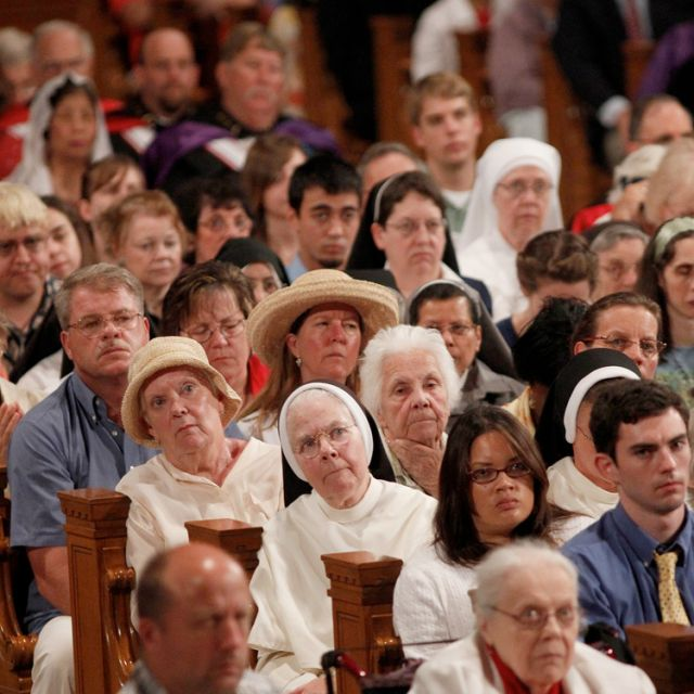 "People listen as Philadelphia Archbishop Charles J. Chaput delivers the homily during Mass at the basilica of the National Shrine of the Immaculate Conception in Washington July 4, the final day of the bishops' ""fortnight for freedom"" campaign."