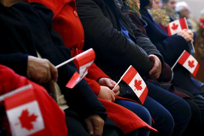Syrian refugees hold Canadian flags as they take part in a welcome service in 2015 at a church in Toronto.