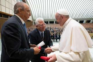 Pope Francis greets Dr. Ramon Tallaj, founder and chairman of the board of Somos Community Care, and Mario J. Paredes, chief executive officer, during a Sept. 20, 2019, symposium at the Vatican on the health care needs of immigrants.