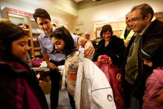 Canadian Prime Minister Justin Trudeau helps a young Syrian refugee try on a winter coat after she and others arrived Dec. 10, 2015 from Beirut at the Toronto Pearson International Airport.