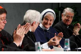 Sister Sharon Holland, president of the Leadership Conference of Women Religious, second from left, receives applause after speaking at a Dec. 16 Vatican press conference for release of the final report of a Vatican-ordered investigation of U.S. communit ies of women religious. From left are: Brazilian Cardinal Joao Braz de Aviz, prefect of the Congregation for Institutes of Consecrated Life and Societies of Apostolic Life; Sister Holland; Sister Agnes Mary Donovan, coordinator of the Council of Major Superiors of Women Religious; and Jesuit Father Federico Lombardi, the Vatican spokesman. The 5,000 word report summarizes problems and challenges the women see in their communities and thanks them for their service. The visitation was carried out between 2009 and 2012.