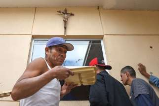 Migrants receive food at San Jose Obrero Parish in Mexicali, Mexico, Feb. 26. Between 60 and 80 migrants receive food at the parish every day.