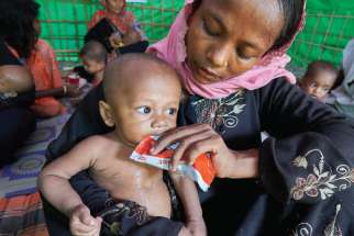 A woman from Myanmar feeds her child in a UN clinic for severely malnourished Rohingya children Oct. 28 in the Balukhali Refugee Camp near Cox's Bazar, Bangladesh. More than 600,000 Rohingya have fled government-sanctioned violence in Myanmar for safety in Bangladesh.