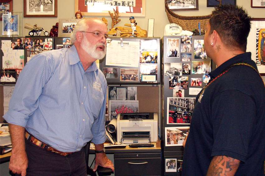Jesuit Fr. Greg Boyle, who founded Homeboy Industries in 1988 to provide hope and  jobs for former gang members, talks to a youth in Los Angeles in 2009.