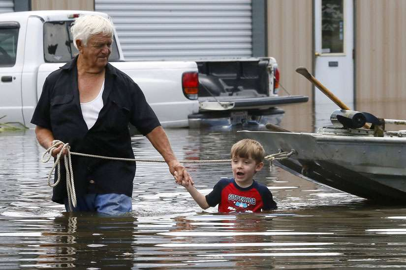 Richard Rossi and his 4-year-old great-grandson Justice wade through water Aug. 15 after their home flooded in St. Amant, La.