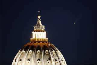 "The comet ""Neowise"" is seen in the sky behind the dome of St. Peter's Basilica in Rome July 13, 2020."