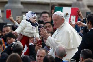 A guard lifts a baby for Pope Francis to greet as the pope leads his general audience in St. Peter's Square at the Vatican Nov. 6, 2019.
