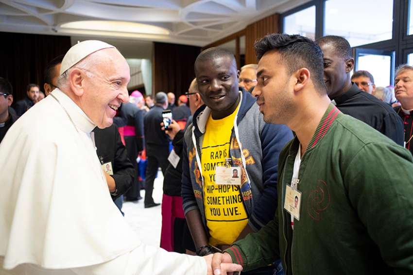 Pope Francis greets a youth delegate before a session of the Synod of Bishops on young people, the faith and vocational discernment at the Vatican Oct. 4.