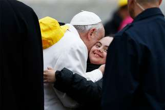 Pope Francis embraces a young woman as he meets the sick and people with disabilities during his general audience in St. Peter's Square at the Vatican April 4.