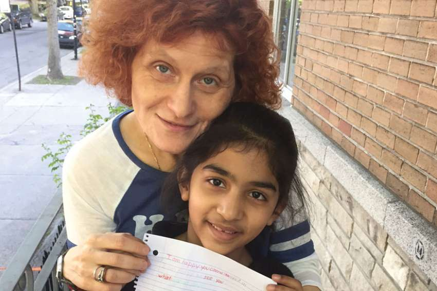 Alessandra Santopadre with a child the Montreal archdiocese's refugee office is helping as her family seeks refugee status.