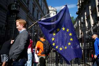 A man carries a European Union flag in London June 24, a day after voters in the United Kingdom decided to leave the EU.