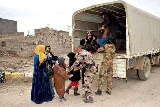 Iraqi soldiers evacuate families from Ramadi, Iraq, Feb. 3, after the city was recently recaptured by Iraqi forces. A European bishops' commission has welcomed a move by the European Parliament to classify atrocities and religious cleansing by the Islamic State as genocide. Canada has been asked to follow suit but has not done so to date.