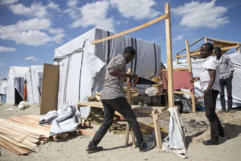 "Sudanese men build a structure to house them in the ""Jungle"" migrant camp near Calais, France, Aug. 5. Catholic bishops from France and Britain have urged their governments to settle a growing refugee crisis around the port of Calais, where highways have been blocked and migrants from Africa and the Middle East have died attempting illegal crossings of the Channel Tunnel."