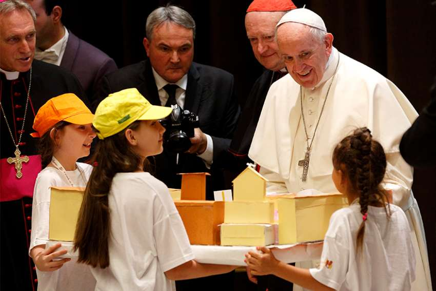 "Pope Francis accepts a gift during an audience with children participating in the ""Train of Children"" at the Vatican June 9. Children from poor suburbs outside Milan arrived on a train that stopped at the Vatican."