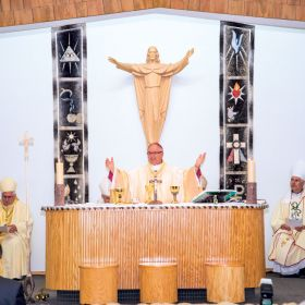 Moments after his ordination, Bishop Tony Krotki leads a packed Mary our Mother Church in the Eucharist. The Oblate missionary from Poland arrived in Canada in 1990 unable to speak English. Today he celebrates Mass and converses with the people of Nunavut in Inuktitut. The banners behind the altar are made from seal skin, while the crucifix to the right of the altar stands on a carved narwhal tusk sitting in a caribou antler base. At left is Ottawa Archbishop Terrence Prendergast, while Bishop Murray Chatlain of Mackenzie-Fort Smith is at the right.