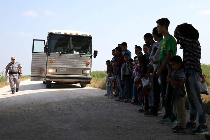 Immigrants turn themselves in to Border Patrol agents April 2 after illegally crossing the border from Mexico into the U.S., and wait to be transported to processing center near McAllen, Texas.