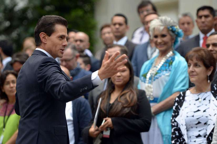 Mexican President Enrique Pena Nieto speaks with citizens in late May outside the presidential residence in Mexico City. How much the same-sex marriage issue and Catholic Church intervention, along with the intervention from evangelical congregations, swayed Mexico's recent elections remains disputed.