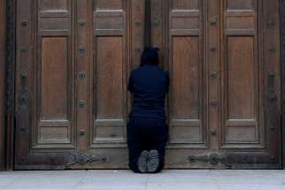 A person prays at the closed doors of London's Westminster Cathedral on Easter, April 12, 2020, during the COVID-19 pandemic. Churches in England and Wales must wait until July before they may reopen under a coronavirus recovery strategy published by the government.