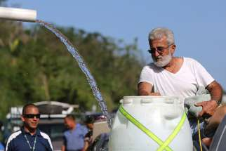 A man fills a plastic drum with spring water from a mountain in Utuado, Puerto Rico, Oct. 21, 2019. Access to clean, fresh water is a fundamental human right that must be defended, especially in poor areas where men, women and children are suffering the deadly effects of climate change, Pope Francis said.