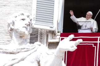 Pope Francis waves as he leads the Angelus from the window of his studio overlooking St. Peter's Square at the Vatican Aug. 15, the feast of the Assumption.