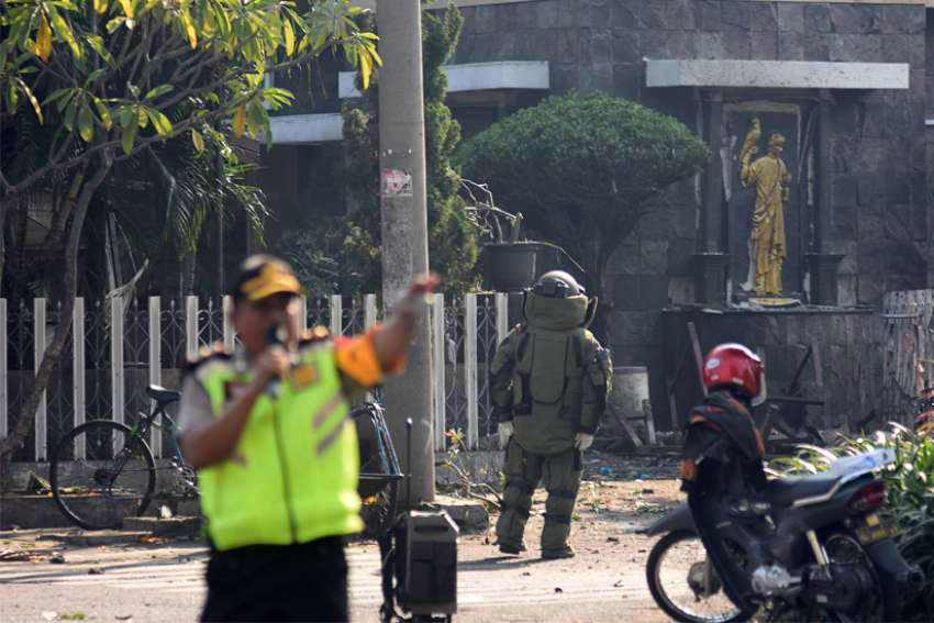 A member of the police bomb squad unit examines the site of a May 13, 2018, explosion outside Santa Maria Catholic Church in Surabaya, Indonesia. Ucanews.com reported Aug. 27 that arrests were made in East Java and that all those arrested were members of the Islamic State-affiliated group Jamaah Ansharut Daulah.