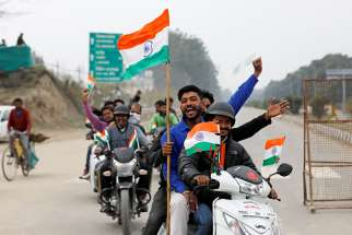 People ride motorbikes on the outskirts of Amritsar, India, March 1, 2019, before the arrival of an Indian air force pilot, who was captured by Pakistan two days earlier and later released. Catholic groups have joined the protest of military escalation in the region.